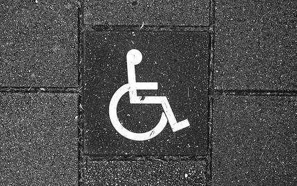 Ausschnitt eines Gewegs aus Betonsteinen mit weißem Rollstuhlpiktogramm