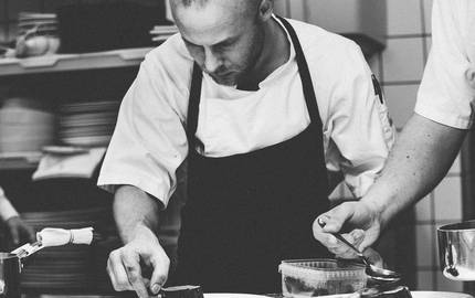 Schwarzweiss Bild das ein Koch beim Tellerfinisch zeigt