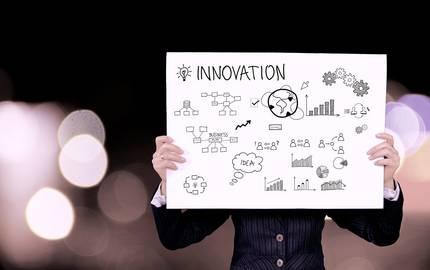Person hebt Plakat mit Innovations-Grafik hoch