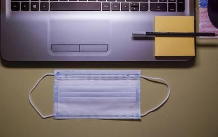 Laptop und Mund-Nasen-Schutz